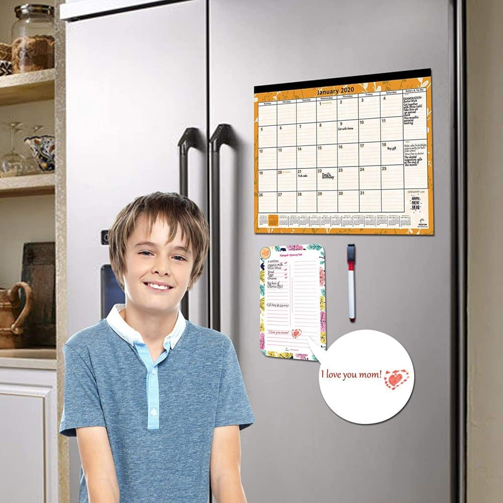 boy smiling beside the large magnetic calendar fro fridge with free dry erase notepad
