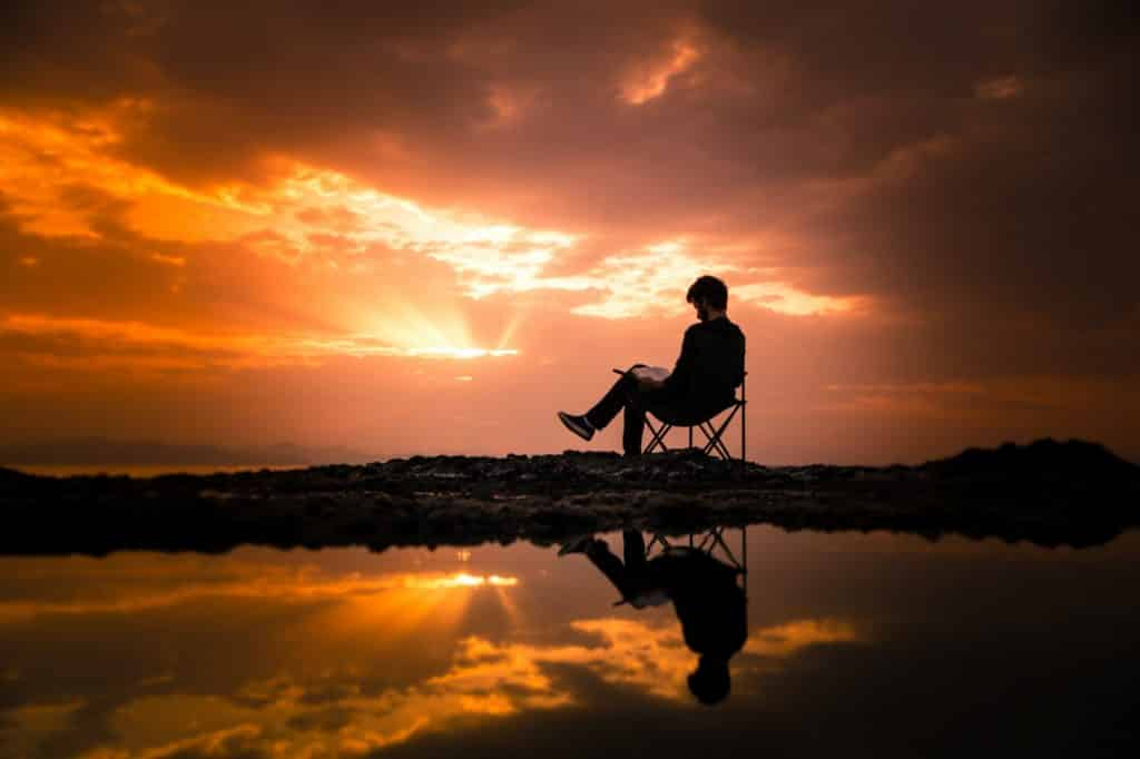 man reading a book during his free time and enjoying the sunset