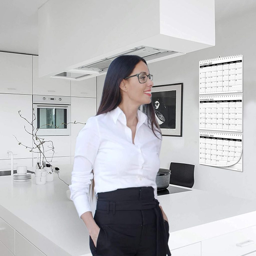woman smiling while looking at the 3 month wall calendar hanging on her wall