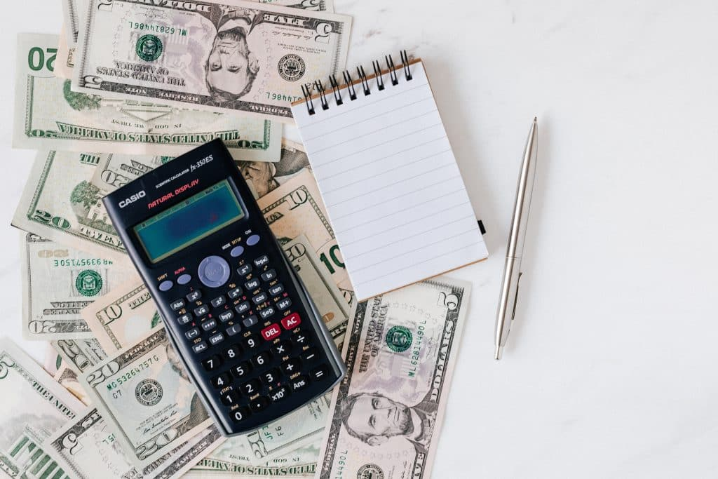 money with calculator, pen and notebook for financial planning